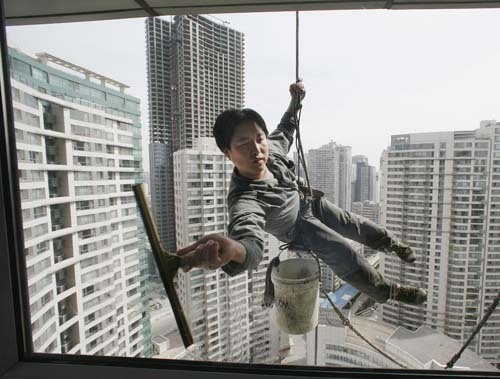 A worker cleans the windows of an apartment block in Beijing's central buisiness district